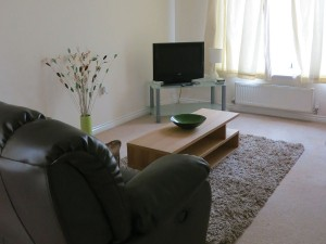 Furnished living room with LCD TV, DVD player and French doors to garden.